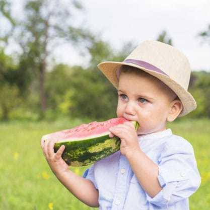 boy eats watermelon on lawn